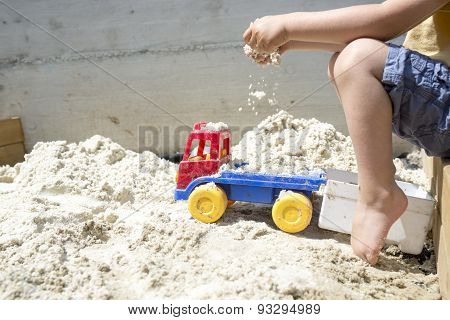 Boy Playing With His Truck Toy At The Beach Sand