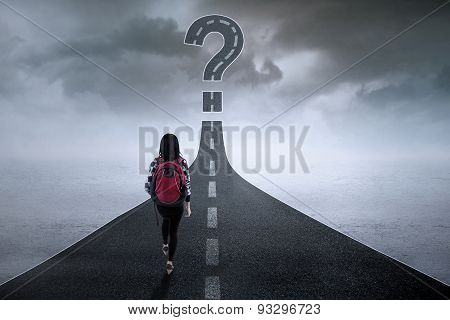Student With Question Sign On The Road