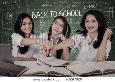 Three Students Joining Hands