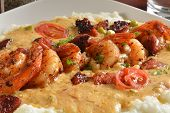 stock photo of creole  - Sauteed shrimp in a creole butter sauce with peppers and vegetable medely on grits - JPG