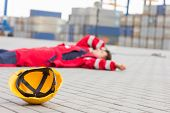 pic of shipyard  - Yellow hardhat at shipyard with depressed male worker lying in shipping yard - JPG