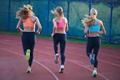 pic of race track  - athlete woman group  running on athletics race track on soccer stadium and representing competition and leadership concept in sport - JPG