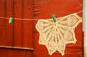 stock photo of knitting  - beautiful handmade knitted serviette hand on the rope with clothespin on the orange wall country house background  - JPG