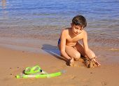 image of preteen  - preteen handsome boy with snorkeling mask and tube build castle from sand on the red sea background - JPG