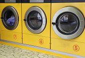 stock photo of laundromat  - three big yellow washing machines in laundromats - JPG