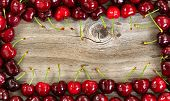 picture of black-cherry  - Border of ripe large black cherries on rustic wood - JPG