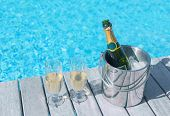 picture of champagne glasses  - Cold champagne bottle in ice bucket and two glasses of champagne on the deck by the swimming pool - JPG