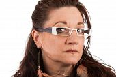 picture of close-up middle-aged woman  - Brunette middle aged woman wearing white framed glasses with a serious expression - JPG