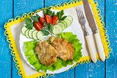 stock photo of pork cutlet  - Fresh hot cutlets of pork lettuce tomatoes and cucumbers on a plate cutlery a napkin with a yellow border on a blue wooden background - JPG