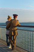 picture of track home  - A girl in a track suit and a guy in his army suit turning away from the camera looking at the sea while standing at the pier at sunset hour on a summer day with no clouds in the sky - JPG
