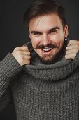 foto of pullovers  - handsome guy with beard and mustache in wool pullover on dark background in studio - JPG