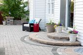 foto of flower pots  - Rounded Steps to Back Door of Luxury Home Stone Patio with Comfortable Wicker Furniture and Flower Pots - JPG
