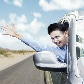 image of car-window  - New car owner driving the car on the road while waving hand through the window - JPG