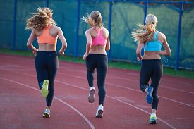 stock photo of race track  - athlete woman group  running on athletics race track on soccer stadium and representing competition and leadership concept in sport - JPG