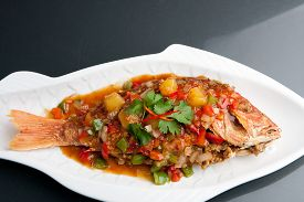 picture of red snapper  - Freshly prepared Thai style whole fish red snapper dinner with tamarind sauce on a white fish shaped plate - JPG