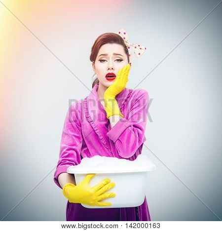 Sad tired young housewife in yellow gloves holding basin with foamed cleanser