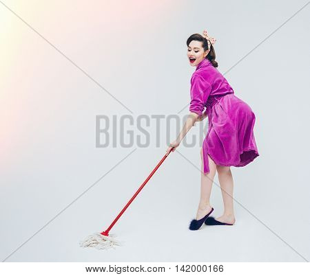 Cheerful playful young woman cleaning the floor with mop