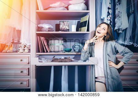 Beautiful young smiling woman choosing at her closet