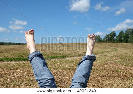 Beautiful playful woman opened bare feet with red nails in rolled blue jeans close-up against summer nature landscape with meadow, sky and country road