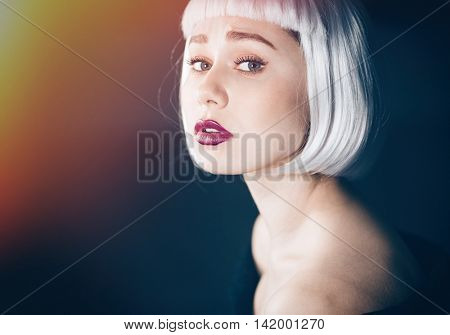 Beauty portrait of attractive young woman in blonde wig over black background