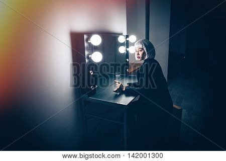 Thoughtful blonde young woman sitting and drinking champagne near the mirror in dressing room