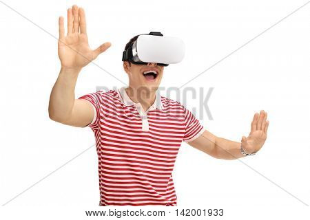 Excited young guy using virtual reality goggles and touching something with his hands isolated on white background