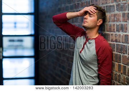 Stressed man suffering from headache in building