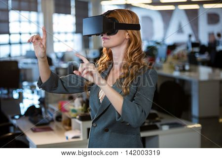 Businesswoman gesturing while using virtual reality simulator in office