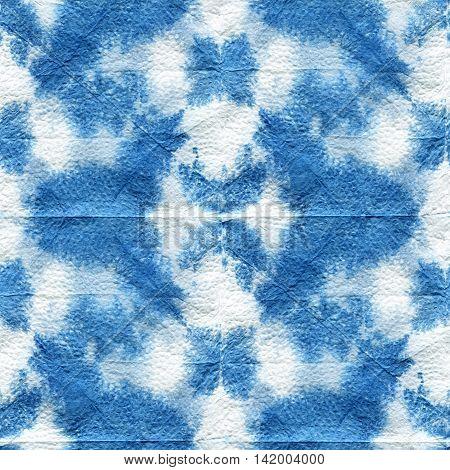 Seamless tie-dye pattern of indigo color with a geometrical ornament. Hand painting fabrics - nodular batik. Shibori dyeing.
