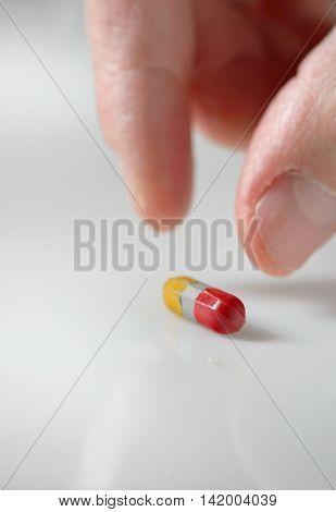 man hand picking up a pill, close up