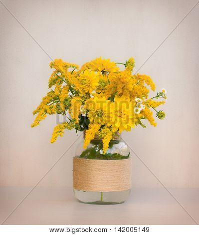 a bouquet of flowers of goldenrod and chrysanthemums in a glass vase homemade closeup on gray background closeup. tinted photo