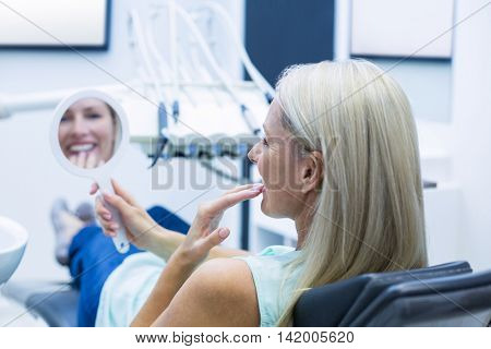 Female patient looking at mirror in dental clinic