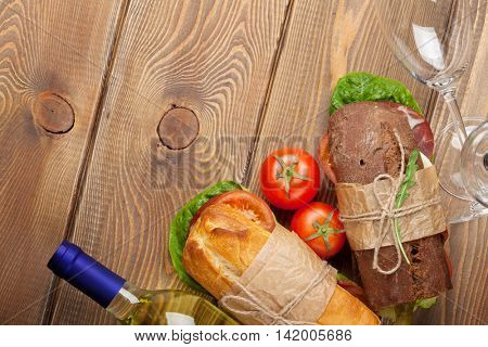 Two sandwiches and white wine on wooden table. Top view with copy space
