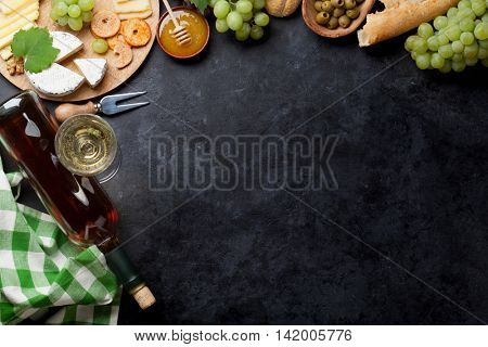 White wine, grape, cheese plate and honey over stone table. Top view with copy space