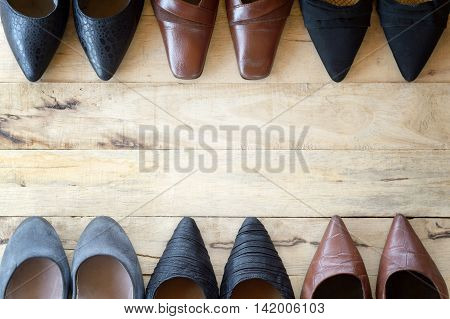 top view of different woman shoe on wooden background several types of high heels