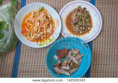 Papaya salad (som tum Thai) with sticky rice grilled beef and Spicy minced pork salad