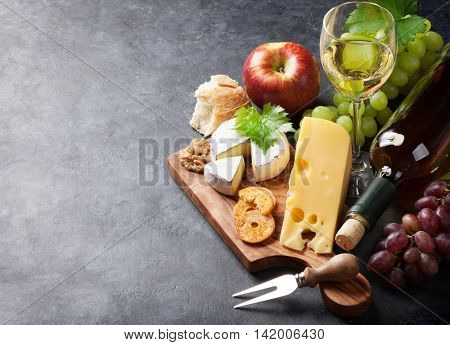 White wine, grape, cheese and apple over stone table. View with copy space