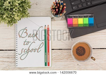 Stationery and text in Notepad: Back to school. Flat lay