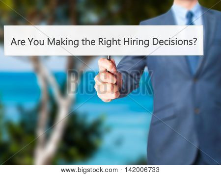 Are You Making The Right Hiring Decisions ? - Business Man Showing Sign