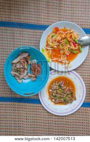Papaya salad (som tum Thai) with sticky rice grilled beef and Spicy minced pork salad on mat
