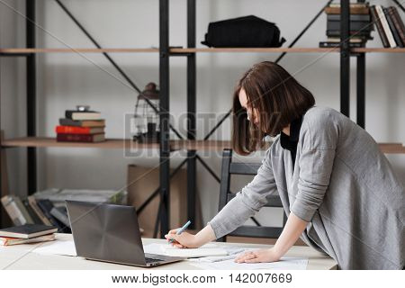 Busy businesswoman standing near table and working with papers in office. Successful business, good worker, reliable manager