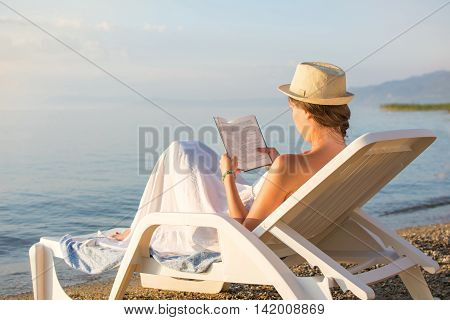 Girl Reading A Book In Sunbed