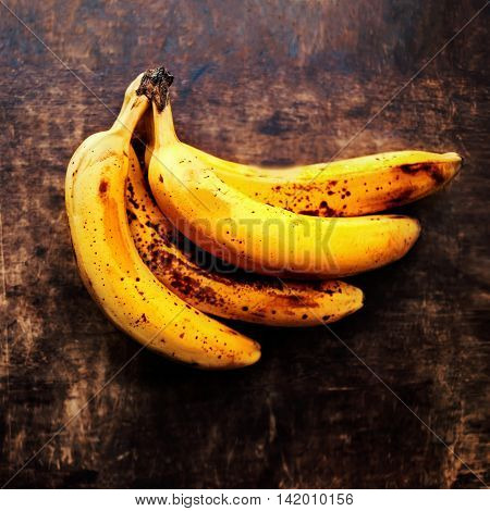 A branch of rotten ripe bananas on vintage wooden background. Overripe banana close up
