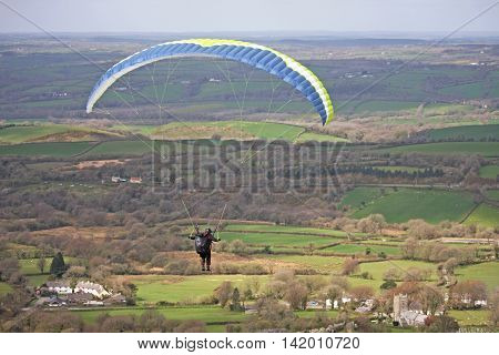 Paraglider flying his wing over Dartmoor, Devon