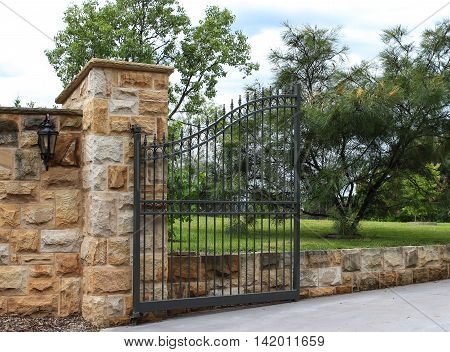 Metal Driveway entrance gate set in large sandstone bricks with garden behind
