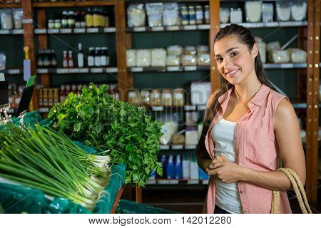 Portrait of woman standing next to scallions and herbs display in organic section of supermarket