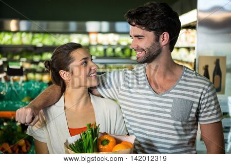 Happy couple with a grocery bag smiling at each other in organic section of supermarket