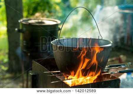 Cooking in sooty bowler on campfire at forest during hike