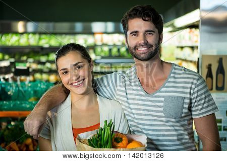Portrait of happy couple standing with a grocery bag in organic section of supermarket
