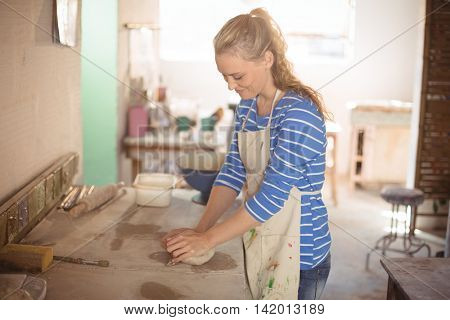 Beautiful female potter molding clay in pottery workshop